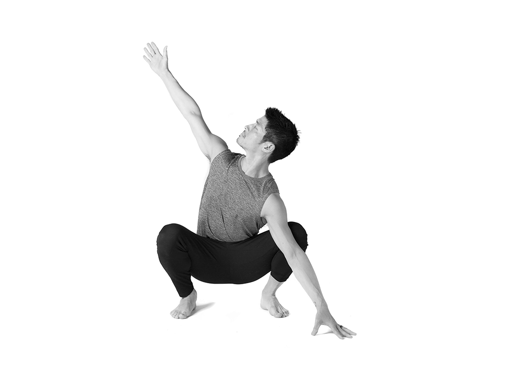 Student practicing Yoga Malasana squat twist