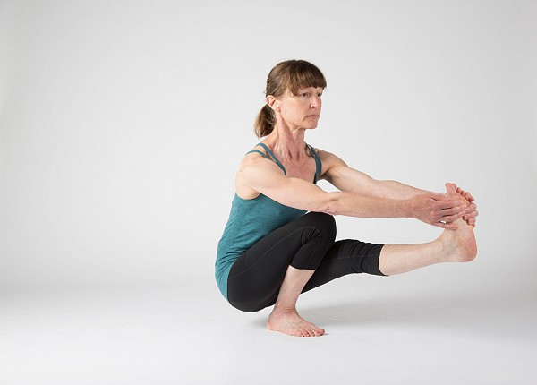 Yoga students practice boat pose.