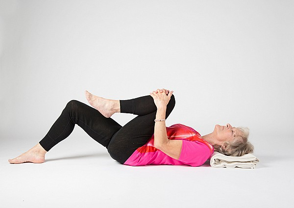 Yoga student in lying knee to chest pose
