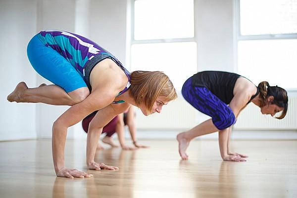 Yoga students practice crow pose