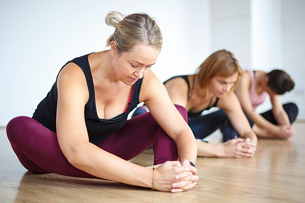 A group of female yoga students in a twisted version of janu sirasana pose