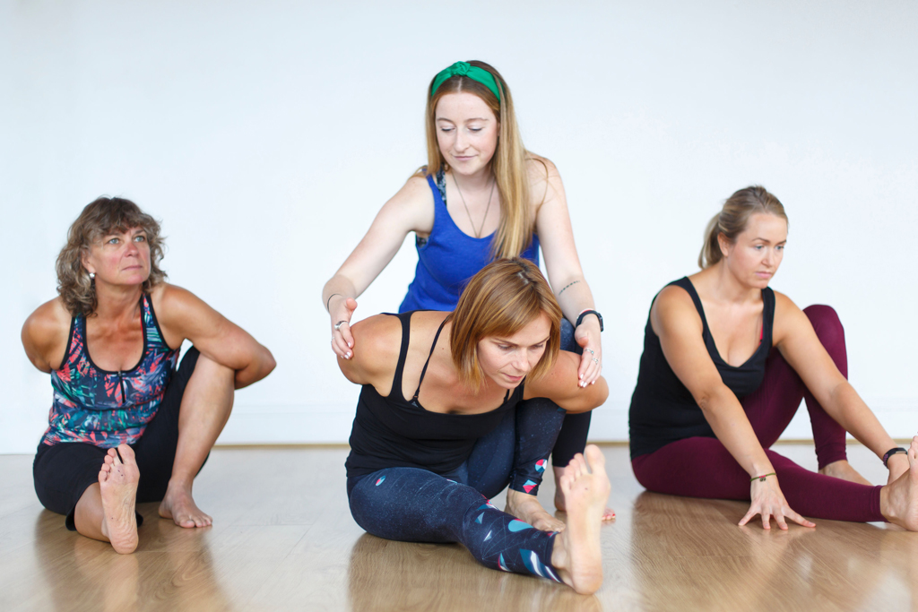 yoga teacher adjusting student in Marychyasana A