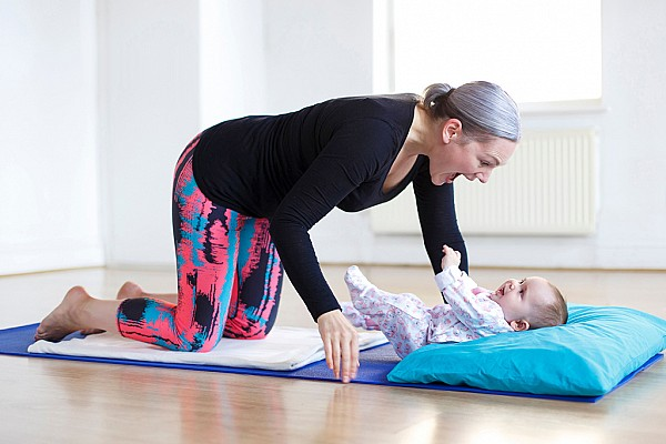 Postnatal mums and babies practicing yoga together