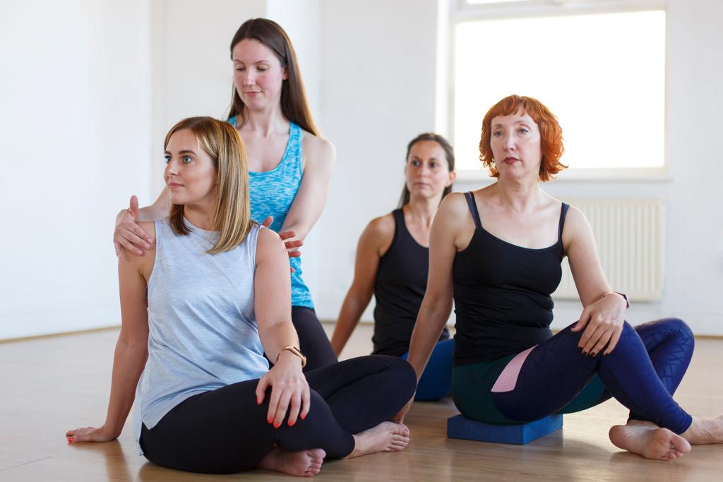 Yoga teacher adjust students in easy cross legged twist