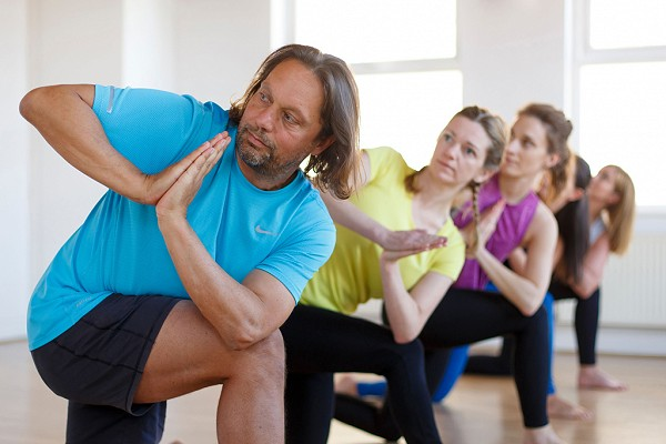 yoga students practice a twist in a lunge