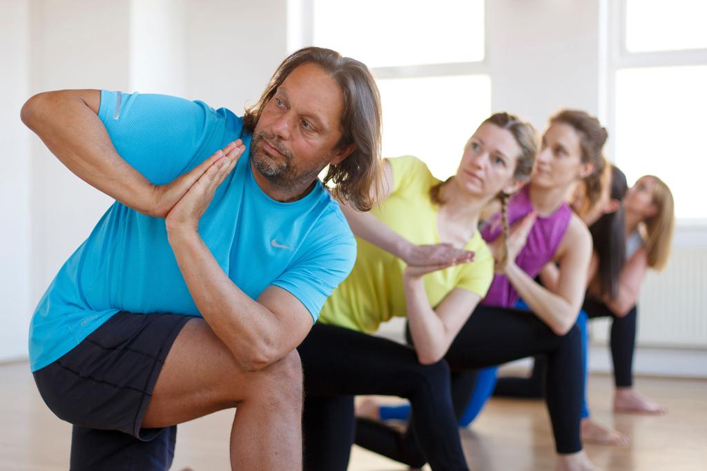 Yoga students practice a kneeling twist
