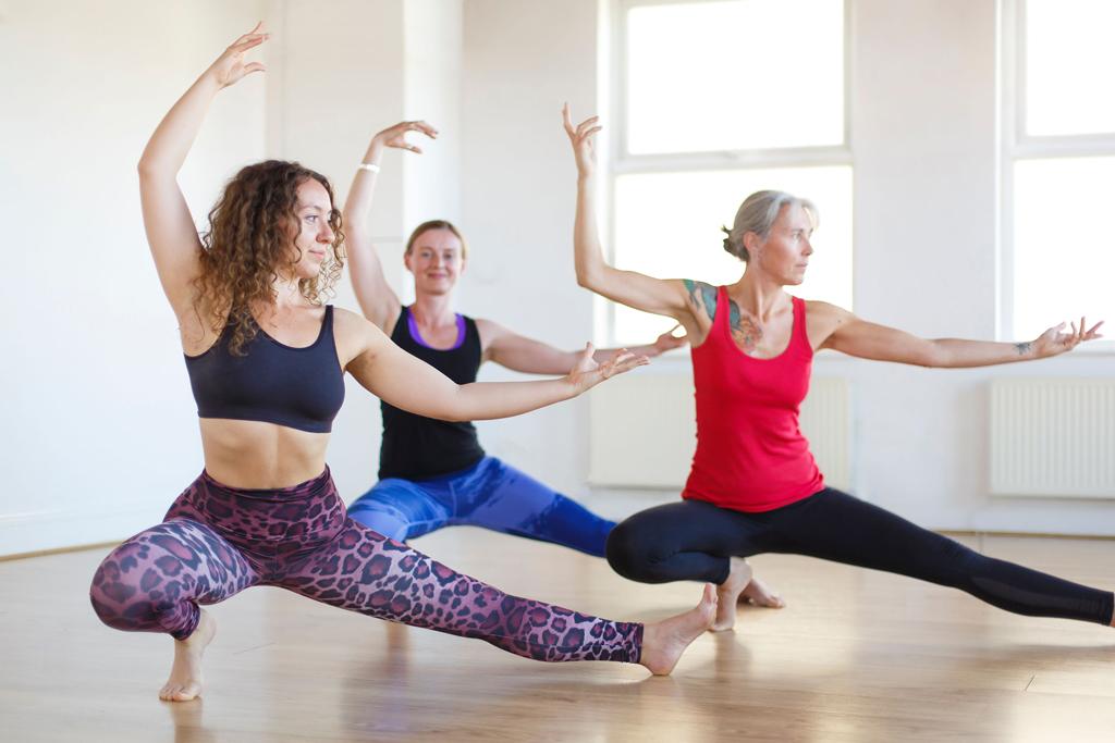 Yoga students are practicing skandasana 2.
