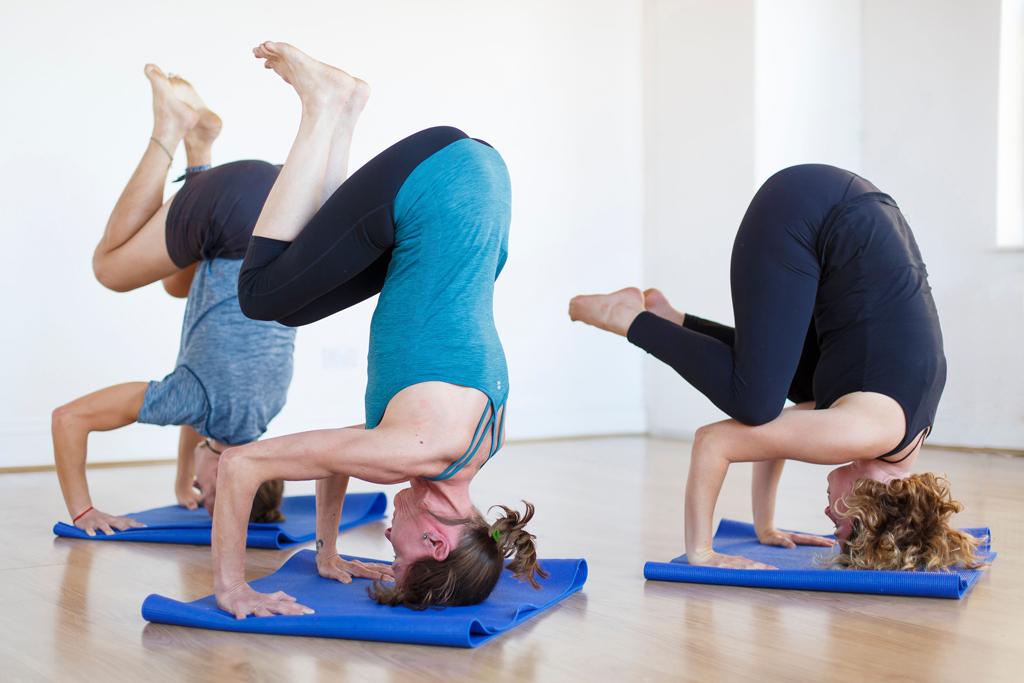 Yoga students practice headstand
