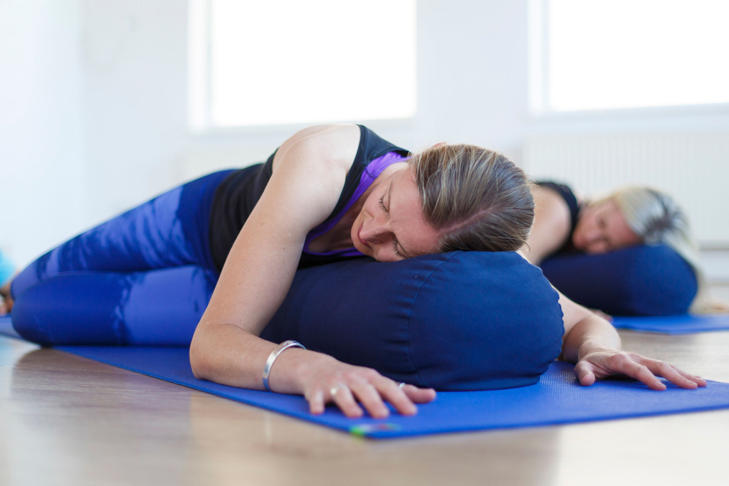 yoga student relaxing over a bolster in a restorative twist
