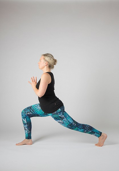 A Yoga teacher is adjusting a students shoulders in a seated twist.