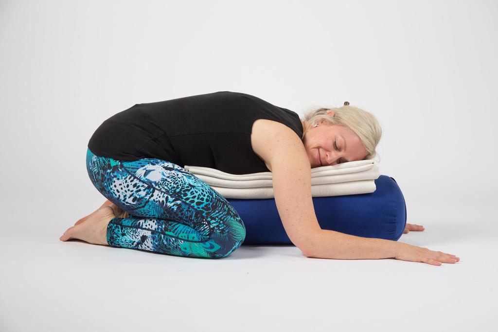 yoga student in supported/restorative child posture