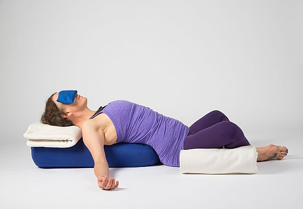 Yoga student practicing restorative baddhakonasana
