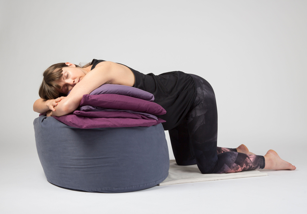 Pregnant yoga student relaxes over beanbag