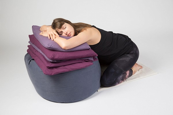 Pregnant yoga student sitting relaxing against props