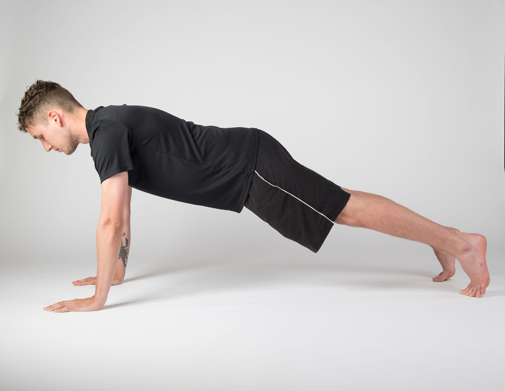 Yoga student practices plank pose
