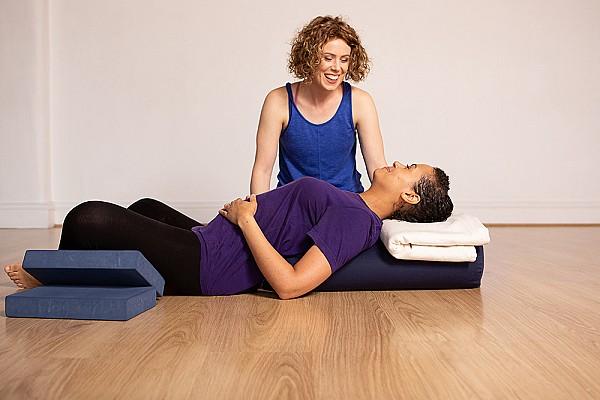yoga teacher helping student in restorative baddhakonasana